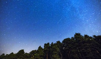 Two Perseid meteors, center and lower left, streak across the sky during the annual Perseid meteor shower during 2014. (AP Photo/Andres Kudacki)