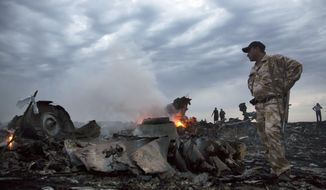 People walk among the debris, at the crash site of a passenger plane near the village of Hrabove, Ukraine, in this July 17, 2014, file photo. (AP Photo/Dmitry Lovetsky, File)