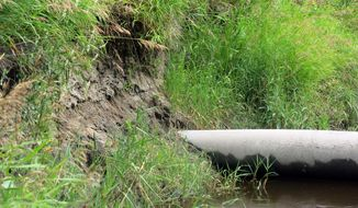 In a July 24, 2014 photo, an Enbridge crude oil pipeline is exposed by erosion where it crosses the Tamarac River in northwestern Minnesota. Three of the seven lines that cross the river are exposed. Floodwater has eroded soil that once buried the pipelines several feet below ground. (AP Photo/MPR News, Dan Gunderson)