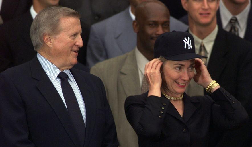 ** FILE ** Then-first lady Hillary Rodham Clinton tries on her new New York Yankees hat as she stands next to Yankees owner George Steinbrenner during an event honoring the 1998 World Series champions on the South Lawn of the White House to honor the 1998 World Series Champions, Thursday, June 10, 1999. (AP Photo/Susan Walsh)