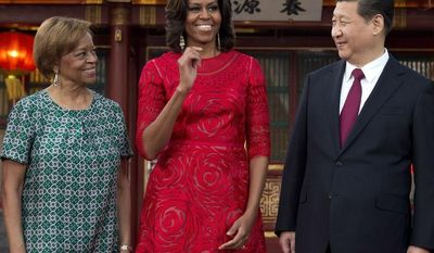 U.S. first lady Michelle Obama, second from left, her mother Marian Robinson, left, share a light moment with Chinese President Xi Jinping, second from right, and his wife Peng Liyuan after a photo session at the Diaoyutai state guesthouse in Beijing, China Friday, March 21, 2014. (AP Photo/Andy Wong, Pool)