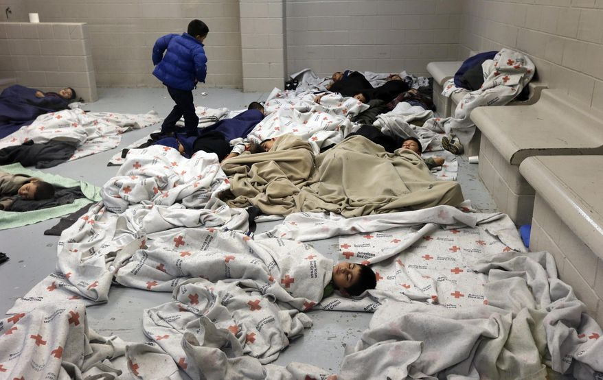** FILE ** In this June 18, 2014, file photo, detainees sleep in a holding cell at a U.S. Customs and Border Protection processing facility in Brownsville,Texas. (AP Photo/Eric Gay, Pool)
