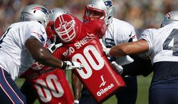 New England Patriots tight end Rob Gronkowski, center, runs a drill with defensive tackle Sealver Siliga, left, and running back James Develin, right, during NFL football training camp in Foxborough, Mass., Saturday, July 26, 2014. (AP Photo)