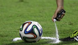 FILE -  In this  June 6, 2014, file photo, a referee uses vanishing spray during a referee's training session in Rio de Janeiro, Brazil. English Premier League referees will start using a vanishing spray to prevent encroachment by players in a defensive wall during free kicks. The water-based, shaving cream-like foam was successfully deployed by FIFA at the World Cup in Brazil and will be used by the Premier League when the new season starts next month. It ensures players lining up in a wall against a free kick respect the 10-yard distance from the ball determined by the referee. (AP Photo/Hassan Ammar, File)
