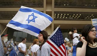 "Lily Goldberg, 13, center, holds a United States flag during a rally in support of Israel in front of city hall in Dallas, Texas, on Wednesday, July 30, 2014. Texas Gov. Rick Perry spoke at the rally, criticizing an American ""policy of calculated ambivalence"" toward Israel, a nod toward conservative voters as he considers a second run for president. (AP Photo/The Dallas Morning News, Brad Loper)"