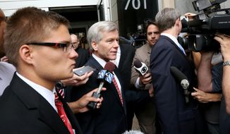 Former Virginia Gov. Bob McDonnell, center, walks by reporters as he leaves the Federal Courthouse in Richmond, Va., Tuesday, July 29, 2014. McDonnell and his wife are charged in a 14-count indictment with accepting more than $165,000 in loans, designer clothes, vacations and a Rolex watch from Jonnie Williams, the CEO of dietary supplements maker Star Scientific. (AP Photo/Richmond Times-Dispatch, Bob Brown)