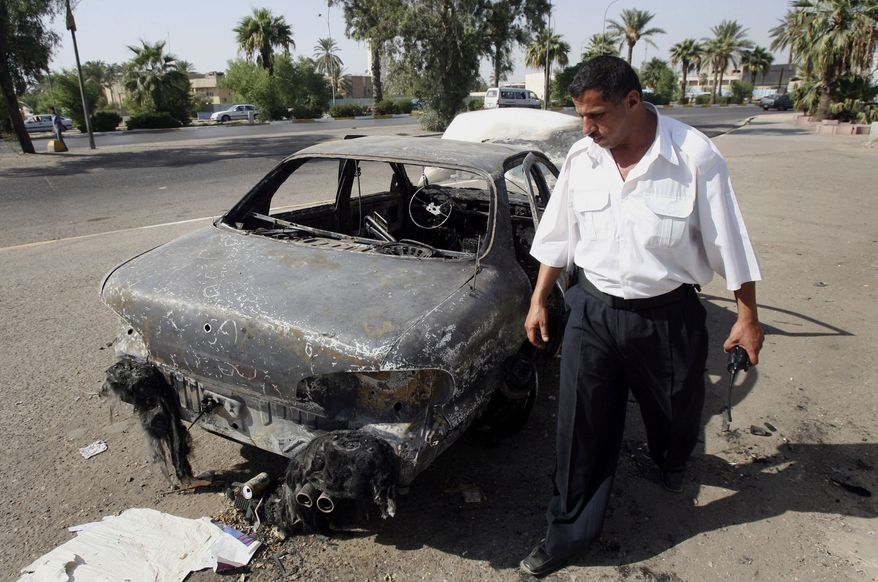 ** FILE ** An Iraqi traffic policeman inspects a car destroyed in al-Nisoor Square in Baghdad, Iraq, Sept. 25, 2007. (AP Photo/Khalid Mohammed, File)