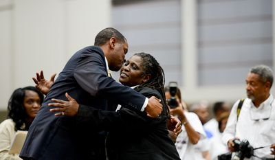 Donnice Tyler, who was formerly homeless and now works at Cambria Suites hugs Hospitality Specialist Ellwood Reid after speaking to audiences about how the Hope Program, a collaboration between Goodwill and University of the District of Columbia Community College, helped get her in a job during Mayor GrayÕs 2014 Citywide Hiring Fair at the Walter E. Washington Convention Center, Washington, D.C., Wednesday, July 30, 2014. (Andrew Harnik/The Washington Times)