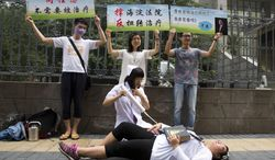 """Gay rights campaigners act out electric shock treatment to protest outside a court where the first court case in China involving so-called conversion therapy is held in Beijing, China, Thursday, July 31, 2014. A gay Chinese man said Thursday he was suing a psychological clinic for carrying out electric shocks intended to turn him straight, as well as the search engine giant Baidu for advertising the center. Words on banners from left read: """"Gays, no need to be treated,"""" """"Support Haidian Court, Against twisted treatment,"""" and """"Ms. Baidu promotes gay treatment by Li Yanhong (Chairman of Baidu)."""" (AP Photo/Ng Han Guan)"""