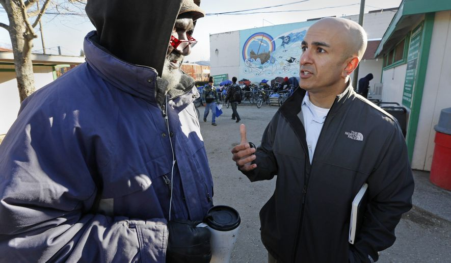 FILE - In this Dec. 4, 2013 file photo, Neel Kashkari, right, who later won the Republican nomination for governor of California, talks with Kenneth Whitaker, 62, at Loaves and Fishes homeless shelter in Sacramento, Calif. In a July 31, 2014 opinion piece published in the Wall Street Journal, Kashkari said he spent a week living as a homeless person in search of a job to test Gov. Jerry Brown's claim that the state is making a comeback after the economic downturn. (AP Photo/Rich Pedroncelli, File)