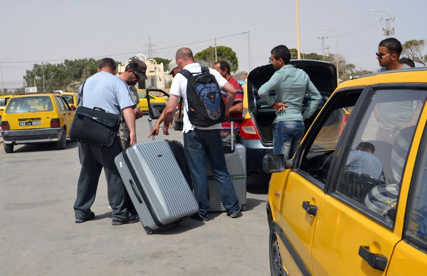 Tunisian taxi drivers wait for clients fleeing from Libya at the border between Libya and Tunisia. Up to 6,000 people a day have fled Libya into neighboring Tunisia this week, the Tunisian foreign minister said, the biggest influx since Libya's 2011 civil war in a sign of the spiraling turmoil as rival militias battle over control of the airport in the capital Tripoli. (Associated press photographs)