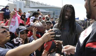 Houston Texans' Jadeveon Clowney, second from right, talks with teammate Duane Brown, right, as they sign autographs for fans after an NFL football training camp practice Sunday, July 27, 2014, in Houston. (AP Photo/David J. Phillip)