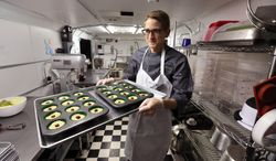 FILE - In this June 19, 2014, file photo, chef Alex Tretter carries a tray of cannabis-infused peanut butter and jelly cups to the oven for baking at Sweet Grass Kitchen, a well-established Denver-based gourmet marijuana edibles bakery which sells its confections to retail outlets throughout the state. Colorado marijuana regulators have drafted an emergency rule aimed at making it easier for new marijuana users to tell how much pot they are eating. (AP Photo/Brennan Linsley, File)