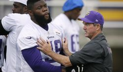 Minnesota Vikings head coach Mike Zimmer instructs defensive tackle Linval Joseph during an NFL football training camp, Saturday, July 26, 2014, in Mankato, Minn. (AP Photo/Charlie Neibergall)