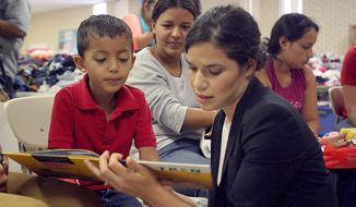 Actress America Ferrera reads a book to a Central American immigrant boy during her visit with the Hispanic Heritage Foundation humanitarian project, Monday July 28, 2014, at a Sacred Heart Church shelter in McAllen, Texas. The program focuses on providing the children with hope and relief from their plight through reading, playing and praying. (AP Photo/The Monitor, Delcia Lopez)