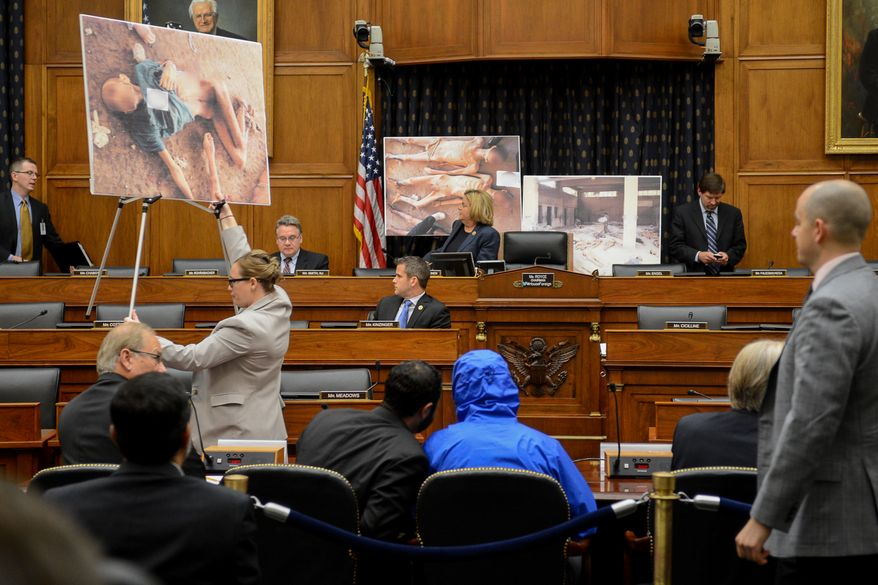 "Photographs of victims of the Assad regime are displayed as a Syrian Army defector known as ""Caesar,"" center, appears in disguise to speak before the House Foreign Affairs Committee at a briefing called ""Assad's Killing Machine Exposed: Implications for U.S. Policy"" concerning the Assad regime, on Capitol Hill, Washington, D.C., Thursday, July 31, 2014. ""Caesar"" was apparently a witness to Bashar Assad's brutality and smuggled more than 50,000 photographs depicting the torture and execution of more then 10,000 dissidents. (Andrew Harnik/The Washington Times)"