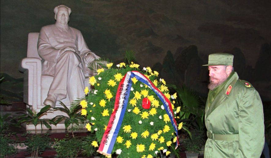 Cuban leader Fidel Castro stands in silence as he pays his respects at a statue of fellow communist revolutionary Mao Tse-tung, in Mao's mausoleum in Beijing's Tiananmen Square Saturday, December 2, 1995. After presenting a wreath Castro viewed Mao's preserved body which is permanently on display in the mausoleum. (AP Photo/Greg Baker)