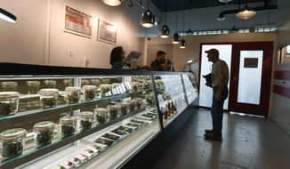 Carl Thomason looks over a case full of marijuana possibilities at the new recreational marijuana store in Manitou Springs, Colo.,, on Thursday, July 31, 2014. Maggie's Farm is the first recreational marijuana store in El Paso County. (AP Photo/The Gazette, Jerilee Bennett)