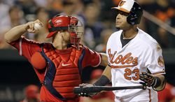 Baltimore Orioles' Nelson Cruz, right, walks off the field in front of Los Angeles Angels catcher Chris Iannetta after striking out swinging in the seventh inning of a baseball game, Thursday, July 31, 2014, in Baltimore. Los Angeles won 1-0 in 13 innings. (AP Photo/Patrick Semansky)
