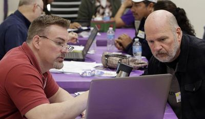 ** FILE ** Keith Saunders, left, a certified Cover California insurance agent, explains a health insurance plan to Mark Tammes at a registration site hosted by Service Employees International Union-United Healthcare Workers, Monday, March 31, 2014, in Sacramento, Calif. (AP Photo/Rich Pedroncelli)