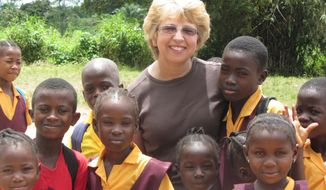 This Oct. 7, 2013 photo provided by Jeremy Writebol show his mother, Nancy Writebol, with children in Liberia. Writebol is one of two Americans working for a missionary group in Liberia that have been diagnosed with Ebola. Plans are underway to bring back the two Americans from Africa for treatment. (AP Photo/Courtesy Jeremy Writebol)