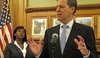 Kansas Gov. Sam Brownback discusses his three new appointments to the state Board of Regents, Friday, Aug. 1, 2014, at the Statehouse in Topeka, Kan. To his left is one of the new board members, Zoe Forrester Newton, a Sedan attorney. (AP Photo/John Hanna)