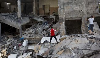 Palestinians inspect a destroyed house in the heavily bombed Gaza City neighborhood of Shijaiyah, close to the Israeli border, Friday, Aug. 1, 2014. A three-day Gaza cease-fire that began Friday quickly unraveled, with Israel and Hamas accusing each other of violating the truce. (AP Photo/Dusan Vranic)