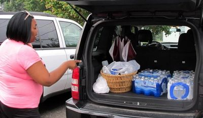 Aundrea Simmons stands next to her minivan with cases of bottled water she bought after Toledo warned residents not to use its water, Saturday, Aug. 2, 2014  in Toledo, Ohio. About 400,000 people in and around Ohio's fourth-largest city were warned not to drink or use its water after tests revealed the presence of a toxin possibly from algae on Lake Erie. (AP Photo John Seewer)