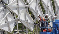 The 36-foot-tall arch that is one of the most recognizable symbols left from the 2002 Winter Olympics is being moved off the University of Utah campus Friday, Aug. 1, 2014, in Salt Lake City. The city became the new caretaker of the arch this week after it was dismantled into 4,000 pieces by the University of Utah at a cost of $116,000. The arch had stood the last 11 years outside Rice-Eccles Stadium after being downtown during the Olympic games, where it graced the medals plaza. (AP Photo/Rick Bowmer)