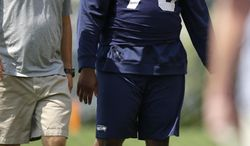 Seattle Seahawks Michael Bowie (73) walks Saturday, Aug. 2, 2014, with Trent Kirchner, Seahawks director of pro personnel during NFL football training camp in Renton, Wash. The team announced Saturday that Bowie would be out 4-6 months due to a shoulder injury. (AP Photo/Ted S. Warren)