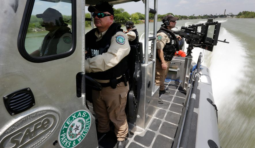 ** FILE ** Texas Parks & Wildlife Wardens patrol the Rio Grand on the U.S.-Mexico border in Mission, Texas. Texas is spending $1.3 million a week for a bigger presence from the Department of Public Safety along the border. (Associated Press)
