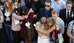 FILE - In this May 24, 2014 file photo, students comfort each other during a candlelight vigil held to honor the victims of the May 23, 2014 mass shooting on the campus of the University of California, Santa Barbara. California Assembly members have proposed AB1014, a bill allowing an immediate family member, therapist or health care provider to go directly to a judge to let law enforcement seize guns from those they deem a danger. (AP Photo/Jae C. Hong, File)