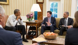 President Barack Obama receives an update from FBI Director James Comey, left, and Attorney General Eric H. Holder, Jr. in the Oval Office. (Official White House Photo by Pete Souza)