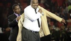 Walter Jones has his gold jacket put on by Walterius Jones, his son and presenter, Friday. Aug. 1, 2014 during the Pro Football Hall of Fame Enshrinees' Gold Jacket Dinner in Canton, Ohio. The induction ceremony will take place Saturday in Canton's Fawcett Stadium. (AP Photo / The Repository, Bob Rossiter)