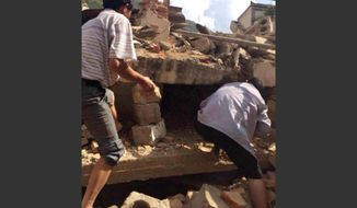 In this photo taken by cellphone and released by China's Xinhua News Agency, men search the rubble of buildings for survivors after an earthquake in Ludian County of Zhaotong City in southwest China's Yunnan Province. (AP Photo/Xinhua/Hu Chao)