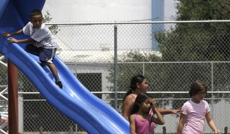 Young children play in a park across the street from the Valero refinery Monday, Aug. 4, 2014, in the Manchester neighborhood of Houston. An Environmental Protection Agency rule to require refineries to monitor emissions of benzene is to be publicly debated Tuesday near Houston. (AP Photo/Pat Sullivan)
