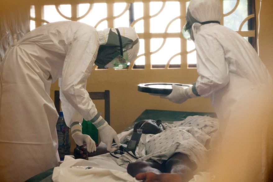** FILE ** In this 2014 photo provided by the Samaritan's Purse aid organization, Dr. Kent Brantly, left, treats an Ebola patient at the Samaritan's Purse Ebola Case Management Center in Monrovia, Liberia. (Associated Press)