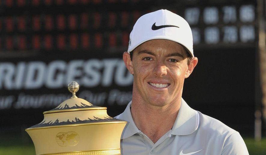 Rory McIlroy, of Northern Ireland, poses with the championship trophy after winning the Bridgestone Invitational golf tournament, Sunday, Aug. 3, 2014, in Akron, Ohio. McIlroy won with a final round 66 to beat Sergio Garcia by two strokes. (AP Photo/Phil Long)
