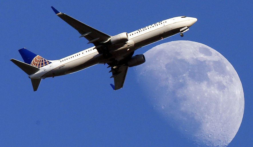 ** FILE ** A United Airlines jet approaches Los Angeles International Airport passes in front of a Waxing Gibbous moon July 17, 2013. ( AP Photo/Nick Ut, File)