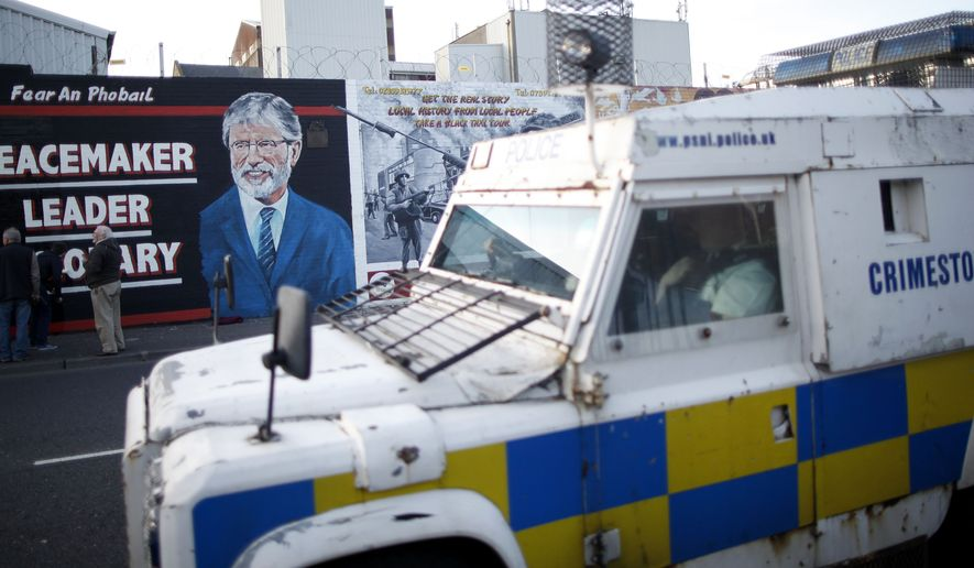 **FILE** A police armored vehicle passes a newly painted mural of Gerry Adams on the Falls Road, West Belfast, Northern Ireland on May, 2 2014. (Associated Press)