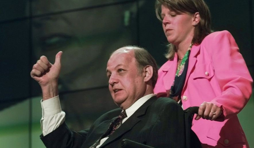 Former Reagan press secretary James Brady gives Clinton s gun-control record a poignant  thumbs up  Monday night, Aug. 26, 1996 on stage at the Democratic National Convention Chicago's United Center in front of a video image of his wife, Sarah Brady. Democrats opened their 42nd national convention Monday with a forceful anti-crime message that echoed from President Clinton s campaign train to the festive hall. The appearance by former Republicans James and Sarah Brady provided a powerful punch to opening night of a convention designed to make the Democrats  case for another term in the White House and a return to power in Congress. Woman is unidentified. (AP Photo/Amy Sancetta)