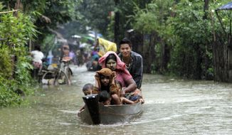 ** FILE ** Local residents ride a boat on a flooded road overflown by the Bago river at a low-lying part in Bago, 80 kilometers (50 miles) northeast of Yangon, Myanmar, Monday, Aug. 4, 2014.   Flooding is common during Myanmar's monsoon season, which typically starts in late May and ends in mid-October. (AP Photo/Khin Maung Win)