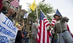 Tom Ratcliffe, right, screams back at chants to oppose immigration Monday, Aug. 4, 2014, outside of Bay City City Hall, in Bay City, Mich. (AP Photo/The Bay City Times, Yfat Yossifor)