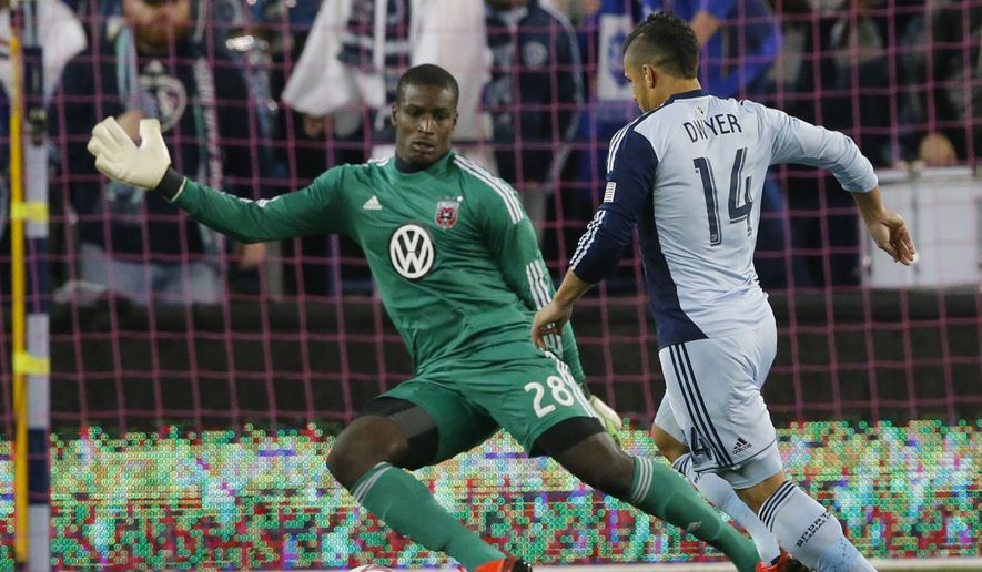 Sporting KC forward Dom Dwyer (14) moves on D.C. United goalkeeper Bill Hamid (28) to score a goal during the first half of an MLS soccer match in Kansas City, Kan., Friday, Oct. 18, 2013. (AP Photo/Orlin Wagner)