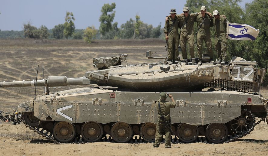 Israeli solders pose for a group photo on a tank before they leave a staging area near the Israel-Gaza border, Tuesday, Aug. 5, 2014. Israel said it withdrew the last of its ground forces from Gaza on Tuesday as it and Hamas began a temporary cease-fire. The calm sets the stage for talks in Egypt on a broader deal for a long-term truce and the rebuilding of the battered, blockaded coastal territory. (AP Photo/Tsafrir Abayov)