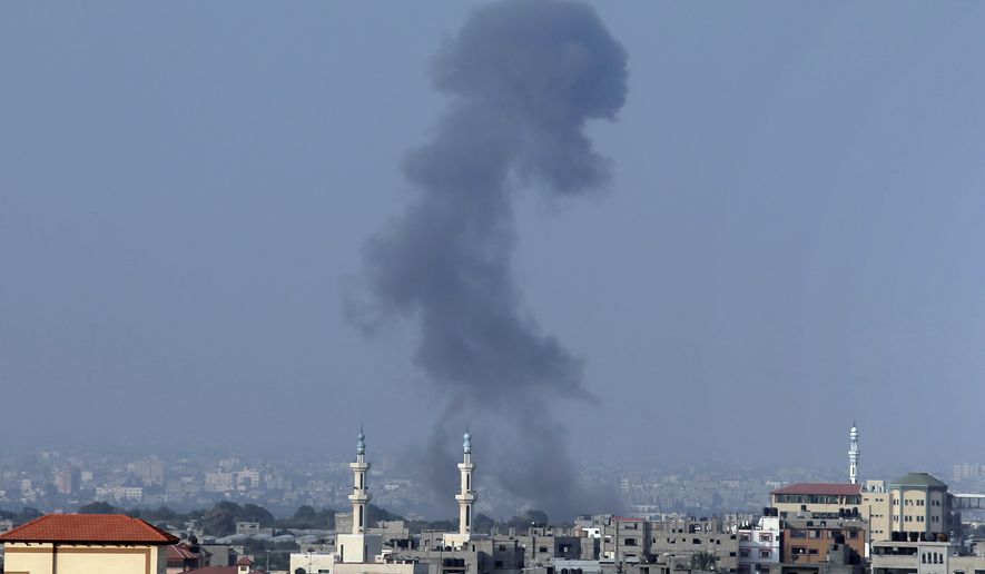 Smoke rises over Gaza City, in northern Gaza Strip, after an Israeli strike, minutes before 8 a.m. (0500 GMT), the time agreed for a preliminary 72-hour cease-fire, on Tuesday Aug, 5, 2014. Israel and Hamas on Monday accepted an Egyptian cease-fire proposal meant to halt a bruising monthlong war that has claimed nearly 2,000 lives, raising hopes that the bloodiest round of fighting between the bitter enemies could finally be coming to an end. (AP Photo/Lefteris Pitarakis)