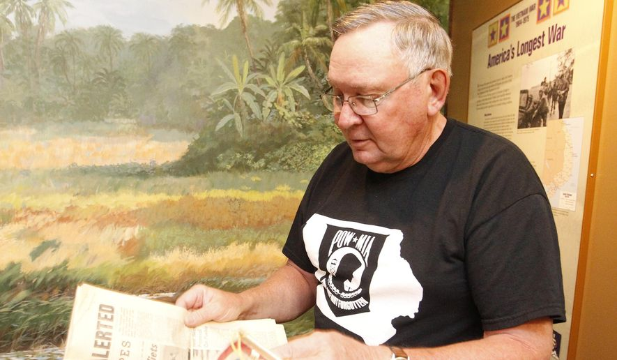 In a Wednesday, July 30, 2014 photo, Tom Brickman pulls out a Stars and Stripes newspaper he had when he was stationed in Vietnam; Brickman donated several items to the Grout Museum to be used in an upcoming exhibit in Waterloo, Iowa.  (AP Photo/Waterloo Courier, Tiffany Rushing)