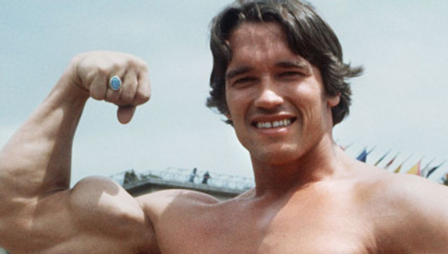 ** FILE ** A young Arnold Schwarzenegger shows off his muscles on the beach. (Associated Press)