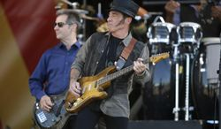 FILE - This May 3, 2014 file photo shows Nils Lofgren, center, performing with Bruce Springsteen and the E Street Band at the New Orleans Jazz and Heritage Festival in New Orleans. Lofgren as forged a relatively unique rock 'n' roll niche through a willingness to sublimate his ego and take on supporting roles with Springsteen, Neil Young and Ringo Starr in addition to writing and recording his own music. (AP Photo/Gerald Herbert, File)