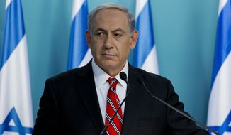 """Israeli Prime Minister Benjamin Netanyahu listens during a press conference in Jerusalem on Wednesday, Aug. 6, 2014. Netanyahu defended Israel's intense bombardment of Gaza, saying that despite the high civilian death toll it was a """"justified"""" and """"proportionate"""" response to Hamas attacks. (AP Photo/Jim Hollander, Pool)"""
